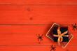 Leinwandbild Motiv Miniature shopping basket with gift and spider on orange wooden background.