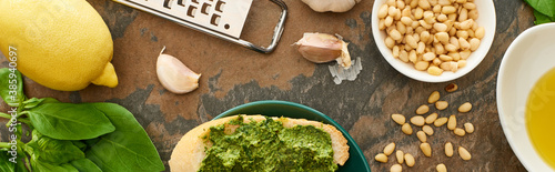 Fototapeta top view of baguette slice with pesto sauce on plate near fresh ingredients and cooking utensils on stone surface, panoramic shot