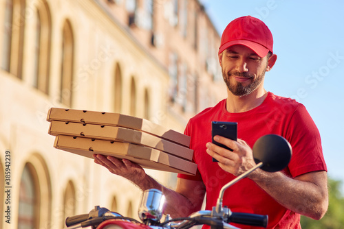 Fototapeta Smiling caucasian male courier with smartphone and pizza obraz