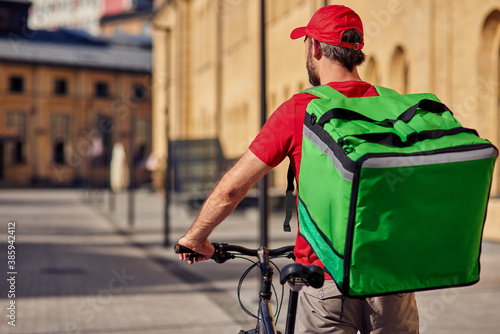 Fototapeta Male courier with refrigerator bag riding bicycle obraz