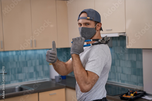 Photo Young caucasian service man in mask showing thumb up