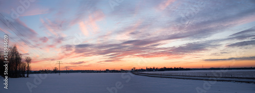 Fototapeta winter landscape in the evening with illuminated clouds, rural scenery with road and cycling track obraz