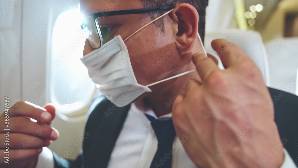 Fototapeta Traveler wearing face mask while traveling on commercial airplane . Concept of coronavirus disease or COVID 19 pandemic outbreak effects on tourism and airline business .