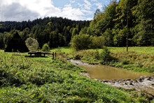 Rest And Picnic Area With Roof Shelter Next To Wild River Stream In Forest. Benches And Table Made Of Wood And Stones. Uhryn, Beskid Sadecki, Poland.