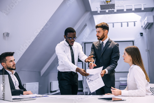 Fotografia angry african businessman points finger at document boss scolds employee for poo