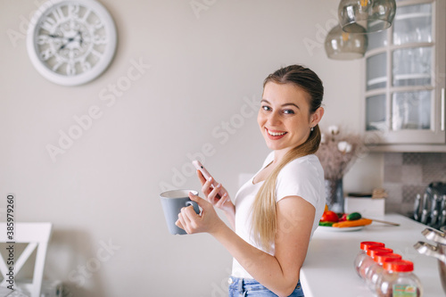young woman reading funny news on phone in the kitchen drinking a cup of coffee.