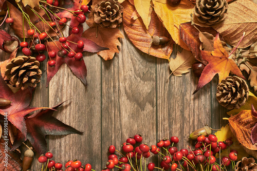 Fototapeta Colorful background with autumn leaves and seasonal decoration on wooden surface obraz