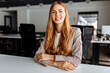 Smiling business young woman sitting at work desk in office