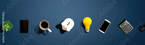 Office supplies with a piggy bank and a lightbulb - flat lay - 385995802