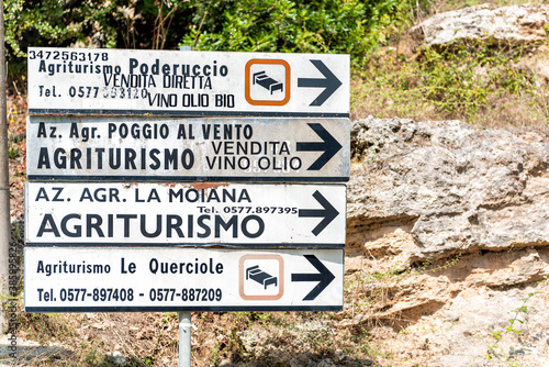Naklejka premium Bagno Vignoni, Italy - August 26, 2018: Medieval town by San Quirico d'Orcia in Val d'Orcia, Tuscany with closeup of direction signs for Agriturismo hotels