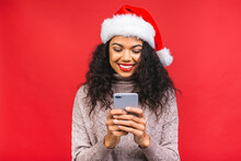 Happy Excited African American Woman In Red Santa Claus Hat With Mobile Phone Isolated Over Red Background.