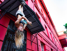 Female Student Hanging By Feet Upside Down Near University And Reading Book. Creative Concept Of Education And Self-development
