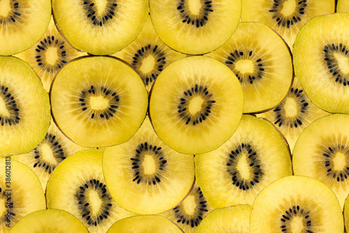 Fototapeta Fruity background composed of many golden kiwi slices
