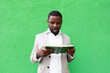 Leinwandbild Motiv African American student with a book on a green background