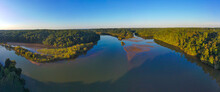 A Breathtaking Panoramic Aerial Shot Of The Bull Sluice Lake And The Chattahoochee River With Clouds, Blue Sky And Lush Green Trees At Morgan Falls Overlook Park  In Sandy Springs, Georgia