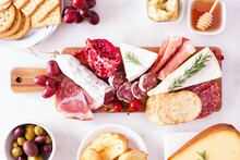 Charcuterie Board Of Assorted Cheeses, Meats And Appetizers. Top View Table Scene On A White Marble Background.