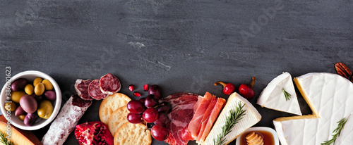 Fototapeta Assortment of cheese and meat appetizers. Top view bottom border on a slate stone banner background with copy space. obraz
