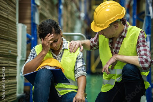 Young African female warehouse worker staff feeling sad and stress while Caucasian man consoling and encouraging due to been fired from job cause by company bankruptcy from coronavirus pandemic Fototapet