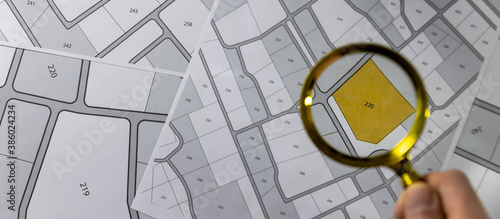 Fototapeta hand with magnifier on cadastre map - search and buy land concept. banner copy space obraz