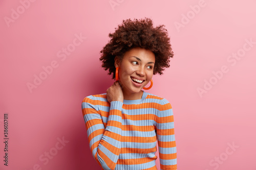 Obraz Photo of curly haired cheerful millennial girl touches neck and looks happily away dressed in casual striped jumper being in good mood isolated on pink studio background. Human emotions concept - fototapety do salonu