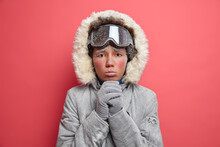 Headshot Of Miserable Displeased Woman With Cold Face Keeps Hands Together Looks With Imploring Expression At Camera Wears Warm Winter Jacket Spends Vacation Actively. Female Mountaineer Has Adventure