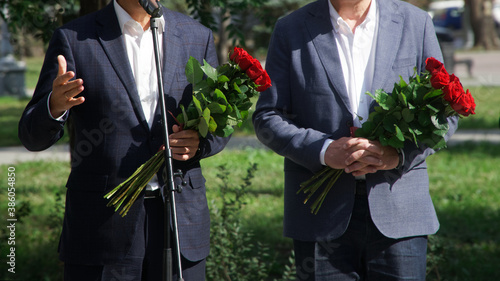 Two officials in suits and bouquets of roses perform at an official event on the Wallpaper Mural
