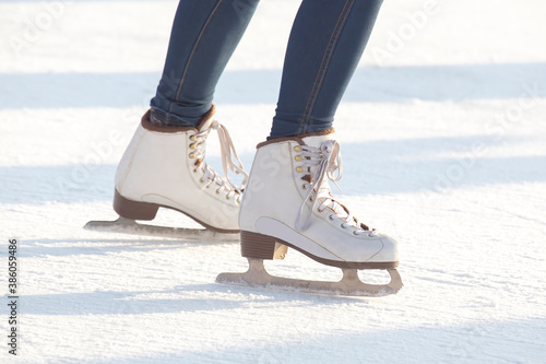 Tablou Canvas legs of a woman in blue jeans and white skates on an ice rink