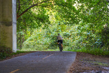 A Man On A Bike Riding On A Hiking Trail Under A Freeway Overpass With Lush Green Trees At The Chattahoochee River National Recreation Area In Sandy Springs Georgia