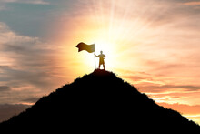 Business Achievement Objective  Target And Successful  Concept , Silhouette Man Standing And Holding Flag On Top Of Mountain With Cloud Sky And Sunlight.