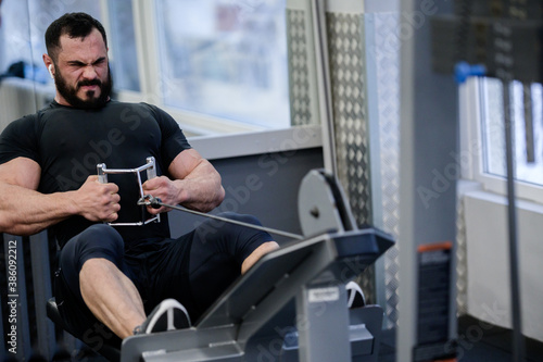 Photo no pain no gain concept of heavy training bearded young athlete male in sport gy