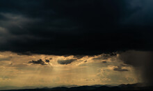 Heaven Sky With God Light Over Mountain Range. Sun Rays Through Dark Clouds. Stormy Sky. Golden Sunlight Shine From Heaven Sky For Hope And Faithful. Landscape Of Mountain Layer. Beauty In Nature.