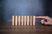 Close-up Fingers Prevent The Wooden Block Jenga Game Stick From Falling Domino Concepts Of Financial Risk Management And Strategic Planning.