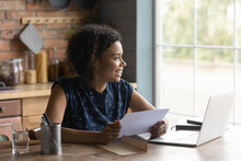 Smiling Millennial Biracial Woman Work On Laptop Read Pleasant Message In Paperwork Correspondence. Happy Young African American Female Feel Excited Optimistic Get Good News In Postal Paper Letter.