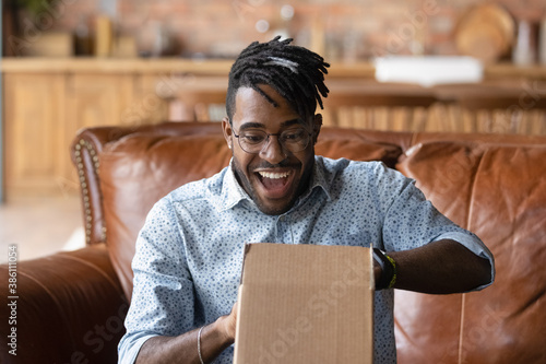 Overjoyed young African American man unpack cardboard box triumph with good quality order Canvas-taulu