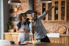 Excited Young Biracial Man And Woman Dance Sing Cooking Together In Modern Design Home Kitchen. Overjoyed Happy African American Couple Have Fun Enjoy Preparing Healthy Food On Weekend.