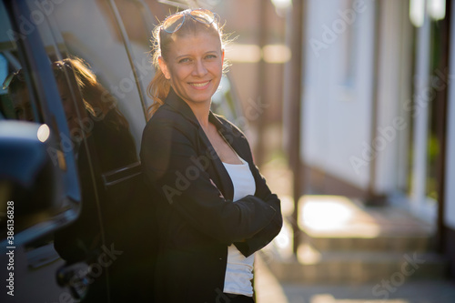 Obraz na plátně Beautiful woman real estate agent in suit and black car