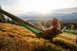 Leinwandbild Motiv Woman hiker resting after climbing in a hammock at sunset
