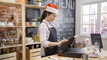 Beautiful Girl Barista In Santa Hat Using Point Of Sale Terminal To Run Successful Coffee Store Business. Female Waitress Celebrating Christmas Holidays In Cafe Bar With Xmas Decor And Using Cash Box