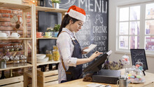 Waitress In Santa Hat And Apron Prepares Bill On Computer POS Tablet Pc In Counter Bar Of Cafeteria. Young Girl Barista Working In Christmas Coffee Shop. Cafe Staff Touching Screen On Sale Terminal.