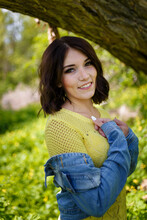 Beautiful Young Woman With Short Hair In Yellow Sweater Among Blossoming Spring Celandine Flowers.