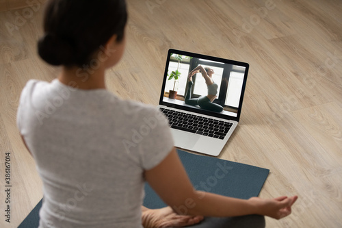 Obraz Rear view sporty Indian young woman practicing yoga at home, sitting in lotus pose on mat on floor, watching webinar online, using laptop, doing exercise, stretching, enjoying fitness activity - fototapety do salonu