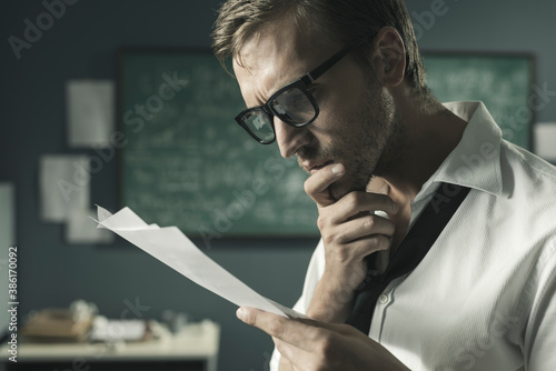 Canvas Print Young mathematician studying in his office and reading papers
