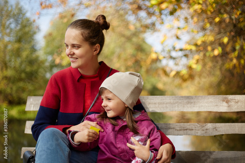 Obraz na plátně Young dark haired mother with daughter sitting on wooden bench in autumn park near lake or river, family having rest by water, mom and little girl looking in distance and enjoying nature