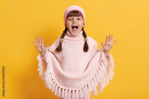 Little happy female child wearing pink poncho and cap yelling happily with raising palms, keeps mouth widely opened, standing against yellow wall, dark haired child with pigtails screaming Canvas Print
