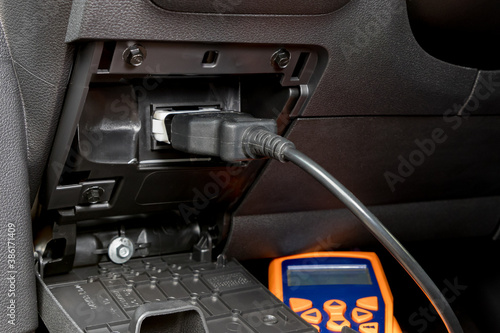 Obraz Engine scan tool plugged into car computer connection. Concept of automotive repair, maintenance, service and vehicle check engine light. - fototapety do salonu