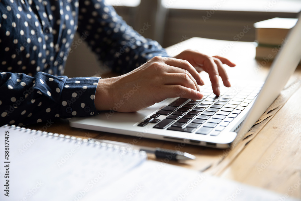 Fototapeta Close up image female hands typing on laptop keyboard. Businesswoman text response to client e-mail, customer buy on-line using web shop services. Internet and modern wireless technology usage concept