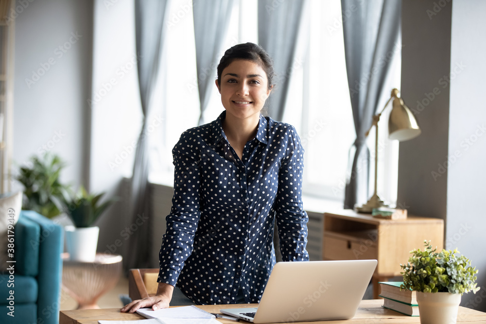 Fototapeta Indian business woman standing near workplace desk smile look at camera feels confident and successful. End of workday, portrait of freelance telecommute work from home, skilled project leader concept