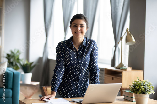 Indian business woman standing near workplace desk smile look at camera feels confident and successful. End of workday, portrait of freelance telecommute work from home, skilled project leader concept