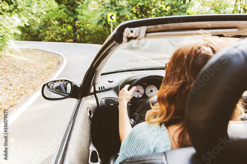 Carta da parati Pretty young woman driving convertible car on summer day