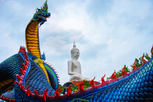 The Blue Naga And The White Buddha Statue. Wat Roi Phra Phutthabat Phu Manorom Is Situated On Phu Manorom, In Tambon Na Si Nuan In The Southern Part Of Amphoe Mueang Mukdahan, Thailand.